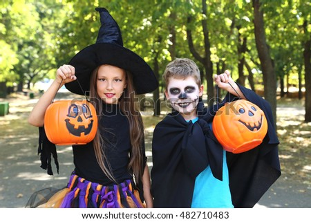 Beautiful girl witch and little boy with basket pumpkin in the park, outdoors
