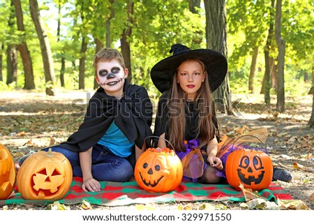 Beautiful girl witch and little boy with pumpkin in the park, outdoors