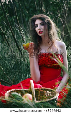 Beautiful Girl, Witch sitting on the Grass in a Red Dress and eat Half an Apple that takes to the Basket