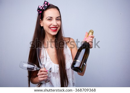 beautiful girl with a bottle of champagne and glasses - stock photo