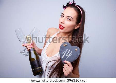 beautiful girl with a bottle of champagne and glasses on Valentine's Day