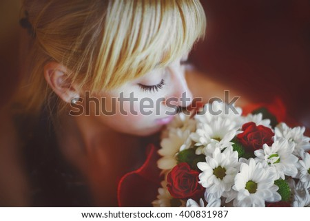 beautiful girl with a bouquet of flowers looking at bouquet