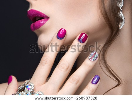 Beautiful girl with a bright evening make-up and pink manicure with rhinestones. Nail design. Beauty face. Picture taken in the studio on a black background.