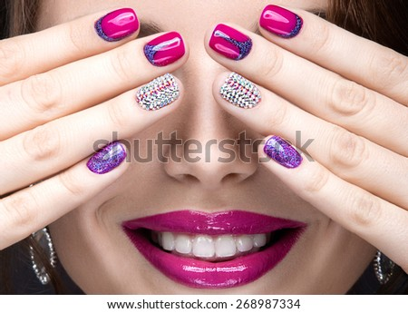 Beautiful girl with a bright evening make-up and pink manicure with rhinestones. Nail design. Beauty face. Picture taken in the studio on a black background. - stock photo