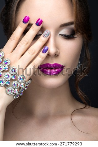 Beautiful girl with a bright evening make-up and purple manicure with rhinestones. Nail design. Beauty face. Picture taken in the studio on a black background.