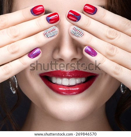Beautiful girl with a bright evening make-up and red manicure with rhinestones. Nail design. Beauty face. Picture taken in the studio on a black background. - stock photo