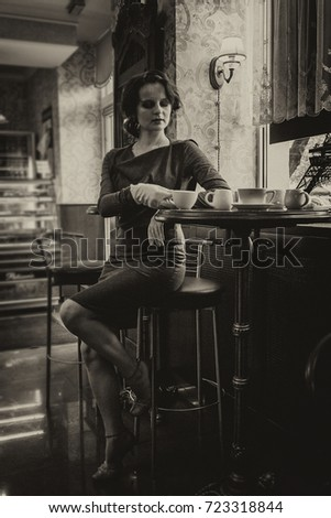 Beautiful girl with a cup of coffee in a cafe, with a touch of sepia close up