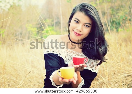 Beautiful girl with a cup of coffee in vintage color tone filter