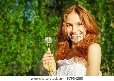 Beautiful girl with a dandelion in his hand - stock photo