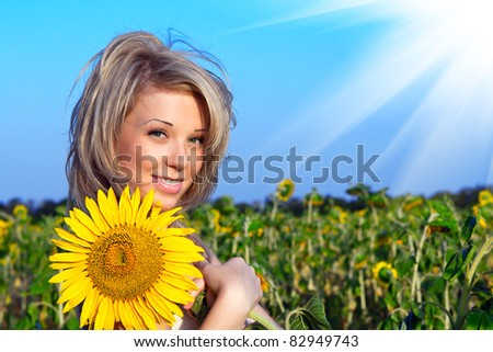 beautiful girl with a flower in the sunflower - stock photo