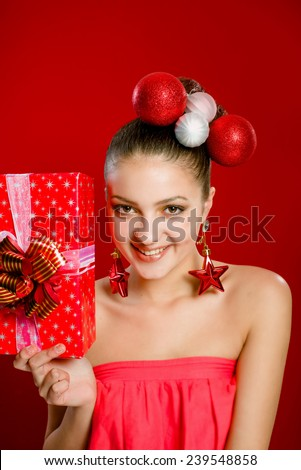 Beautiful girl with a gift box and christmas decorations