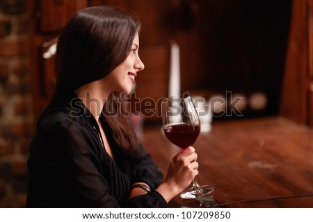 Beautiful girl with a glass in a restaurant - stock photo