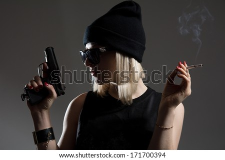 Beautiful girl with a gun in his hand and smoking a cigarette. Blonde in a dark hat in anticipation of an enemy spy - stock photo