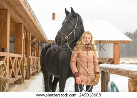 Beautiful girl with a horse near a stable - stock photo