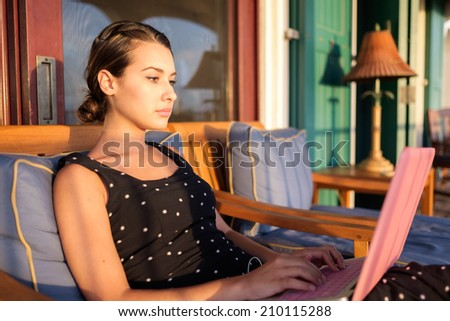 Beautiful girl with a laptop computer in the patio of a home. - stock photo