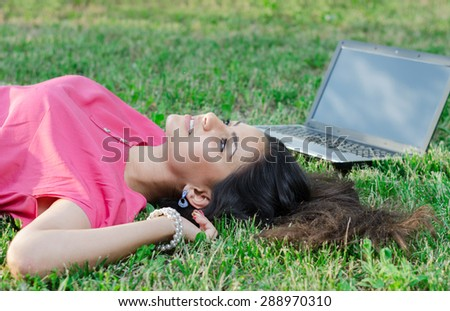 beautiful girl with a laptop lying on the grass