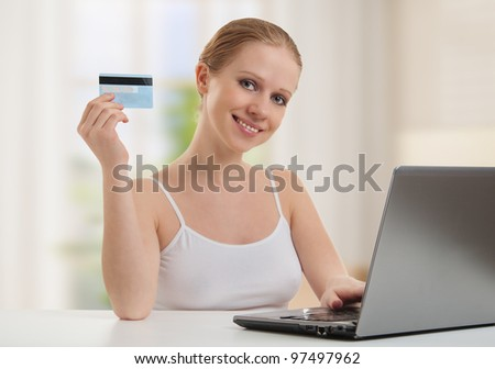 beautiful girl with a laptop makes a payment online using credit cards at home - stock photo