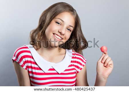 beautiful girl with a lollipop in her hand is posing on a gray background. girl in a dress in red with white stripes. fashion taste