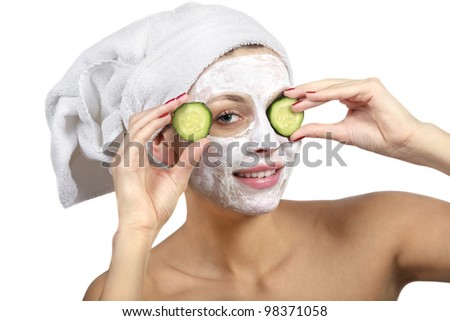 Beautiful girl with a mask and cucumber slices on his face on a white background - stock photo