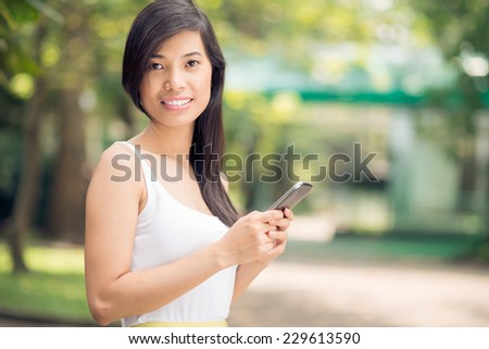 Beautiful girl with a mobile phone looking at the camera - stock photo