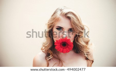 Beautiful girl with a nice flower in mouth