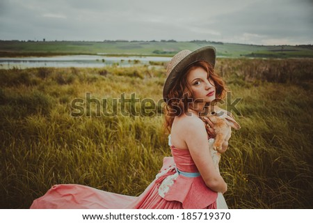 beautiful girl with a rabbit outdoors in summer day - stock photo