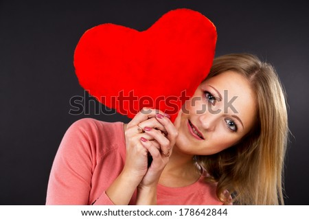 Beautiful girl with a red heart - stock photo