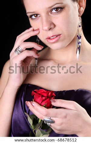 beautiful girl with a red rose on black background