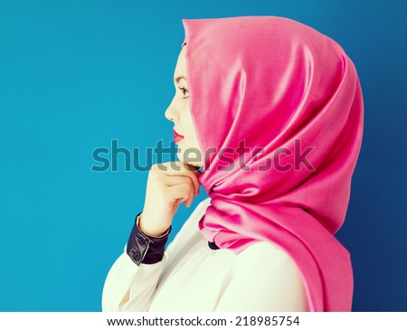 Beautiful girl with a scarf on blue wall - stock photo