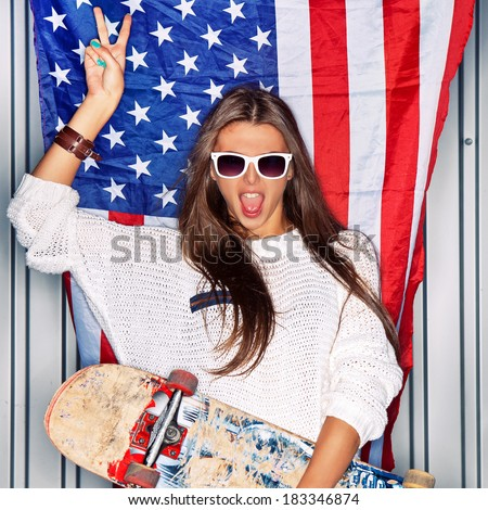 Beautiful girl with a skateboard in front of a flag of the U. S. - stock photo