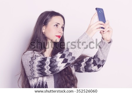 Beautiful girl with a smart phone taking a photograph.