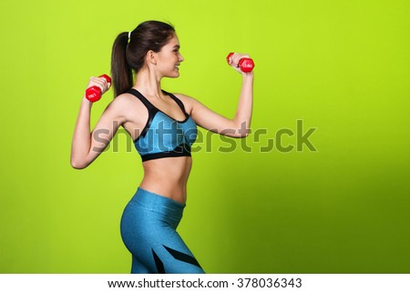 beautiful girl with a sports figure holding a dumbbell on a green background