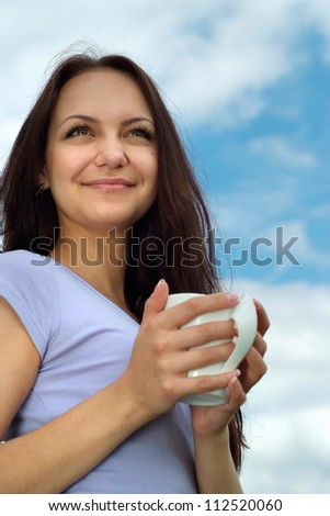 Beautiful girl with a sweet expression on her  face against the blue sky with clouds - stock photo