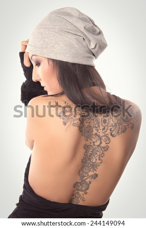 beautiful girl with a tattoo stands in the studio - stock photo