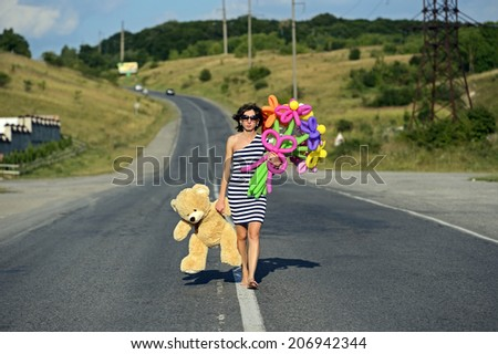 Beautiful girl with a teddybear on the motor road