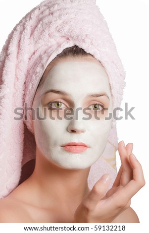 beautiful girl with a towel over her hair and a mask on his face on a white background