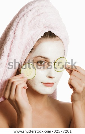 beautiful girl with a towel over her hair and a mask on his face on a white background - stock photo