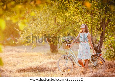 beautiful girl with a vintage bike in the park - stock photo