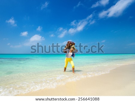 Beautiful girl with a vintage suitcase in a beach - stock photo