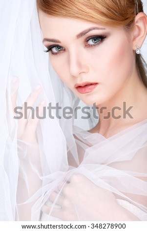 Beautiful girl with a white veill, isolated on a light - grey background, emotions, cosmetics - stock photo