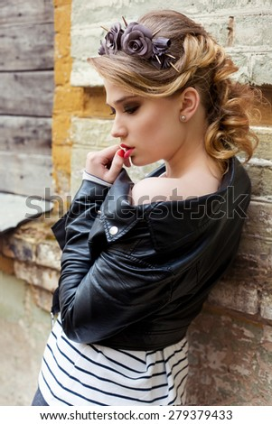 beautiful girl with a wreath of roses and thorns with beautiful hair, makeup smoky and black leather jacket in a rock style stands near the wall of the old building
