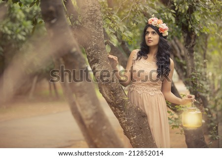 Beautiful girl with a wreath of roses on her head in garden. - stock photo