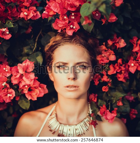 beautiful girl with a wreath on the head of the colors poses a backdrop of red flowers - stock photo
