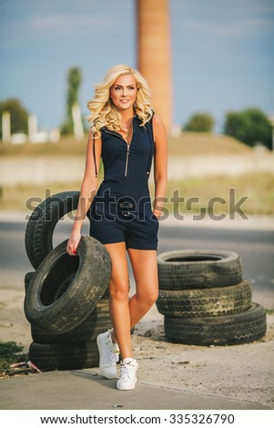 Beautiful girl with automobile tyres - stock photo