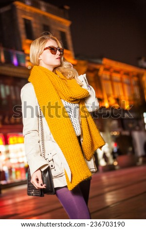 Beautiful girl with bag stay at square in the night - stock photo