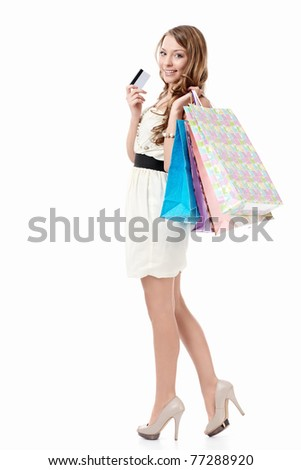 Beautiful girl with bags and credit card on a white background