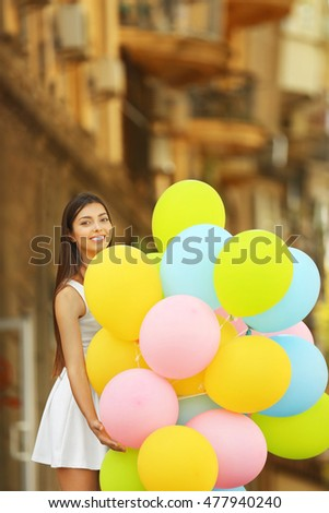 Beautiful girl with balloons on street