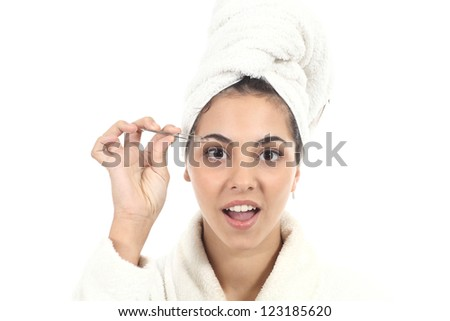 Beautiful girl with bathrobe and towel depilating her eyebrow on a white isolated background
