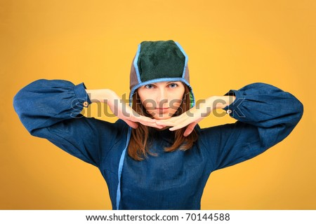 Beautiful girl  with big, blue eyes in strange clothes on orange background - stock photo