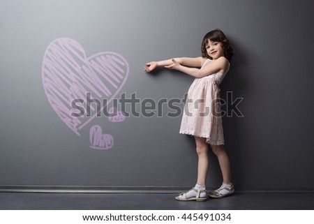 Beautiful girl with big heart and lovely face shows depicted with chalk pink hearts on the neutral background. The power of love of the child. - stock photo